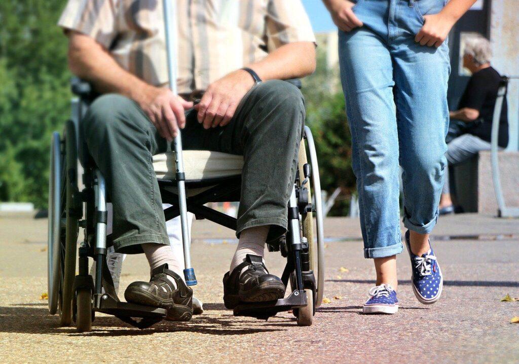 Foto: Uomo su sedia a rotelle accompagnato da un'altra persona