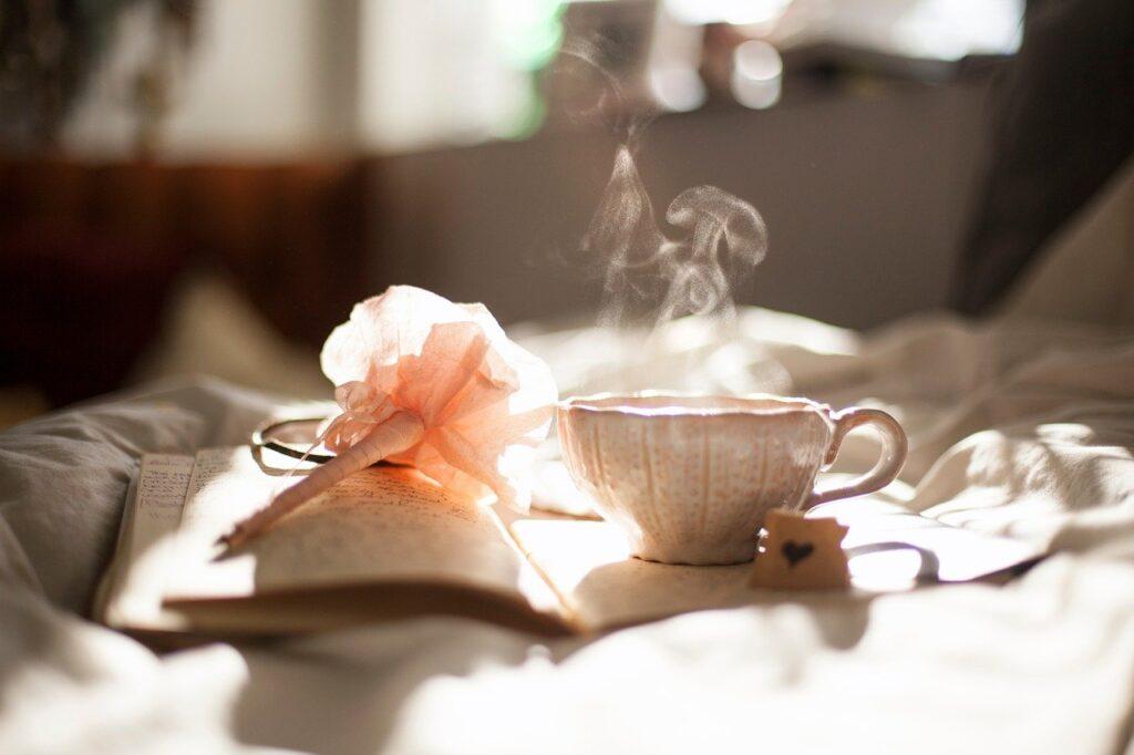 Tazza bianca e rosa fumante su un libro appoggiato su una coperta