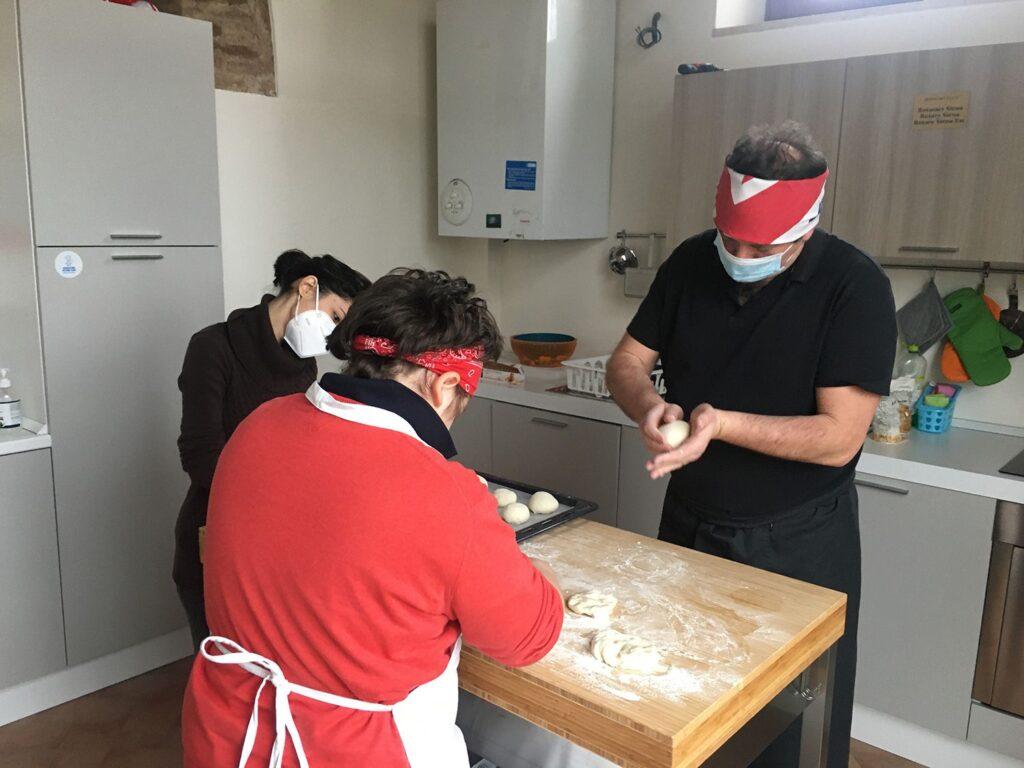 Foto: Tre ragazzi preparano l'impasto per le pizzette